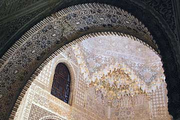Ein Torbogen und Decke im Nasridenpalast in der Alhambra