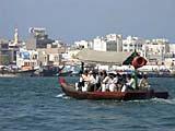 Ein Boot auf dem Dubai-Creek fährt zwischen den Stadtteilen