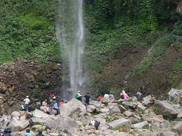 man genießt den feinen Nebel am Grojogou Sewu Wasserfall bei Solo, Java