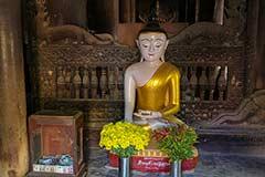 Ein Buddha und Holzverzierungen im Bagaya Kloster der Königstadt Ava in Myanmar