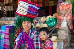 Eine Frau mit Kind trägt am Inle-See ihre Waren auf dem Kopf