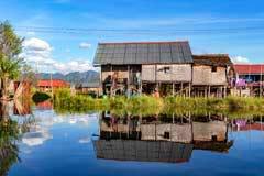 Typisches Pfahlbauhaus mit Spiegelung im Inle-See in Myanmar