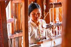 Eine Frau an einem Webstuhl am Inle-See in Myanmar