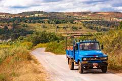 Eine einsame Landstraße mit einem alten Pickup im Osten von Burma