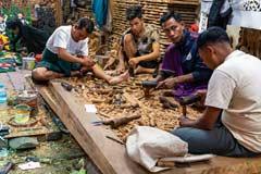 Mehrere Männer schnitzen gemeinsam an einer massiven Holztüre