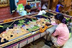 Die Stickerinnen in Myanmar unterlegen das Gestickte mit Watte, um ein Relief zu erzeugen