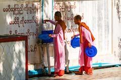 Junge weibliche Mönche ersuchen um Speisung im Mahagandhayon in Mandalay