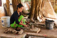 Eine Frau klopft Papyrusmasse so dass die im Wasser ausgelegt und dann getrocknet werden kann