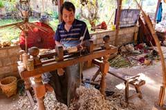 Der Schirmmacher in Pindaya nutzt eine manuelle Drehmaschine, um die Holzstücke zu erstellen