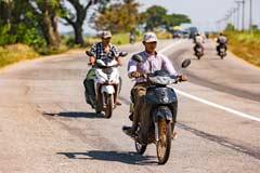 Motorradfahrer auf der gut ausgebauten Strasse von Yangon nach Bago in Myanmar