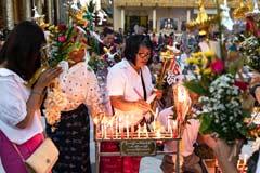 Gläubige in der Shwedagon Pagode zünden Kerzen an