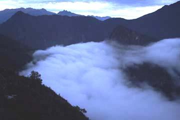 die Wolkendecke schiebt sich über die Ruinen von Machu Picchu, Peru